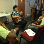 picture of a teacher with two guitar students