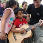 picture of a student showing a child how to play the guitar